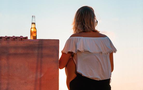 chica de espaldas en una terraza con cerveza